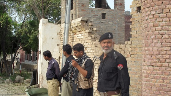 Policemen stand outside the Central Prison after an overnight Pakistan Taliban militant attack in Khyber Pakhtunkhwa on July 30.