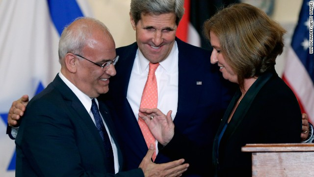 John Kerry (C) looks on as Israeli Justice Minister Tzipi Livni and Palestinian chief negotiator Saeb Erekat (L) shake hands.