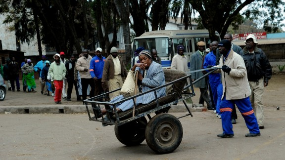 Chizema Najika, an eighty year old voter, arrives to vote at a polling booth in a school in Harare on July 31.