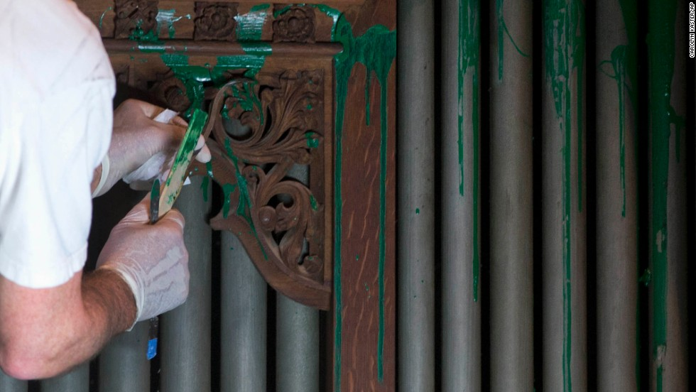 William Adair of Gold Leaf Studios removes paint from the organ in the Bethlehem Chapel on July 30.