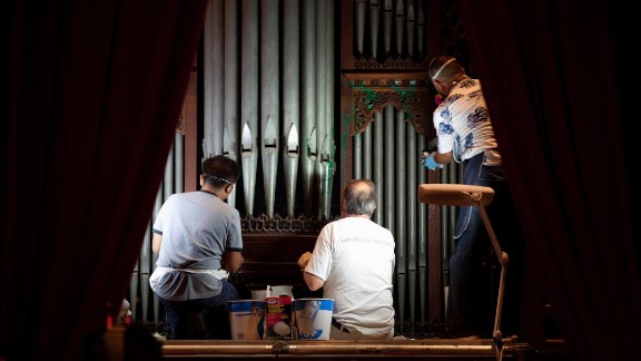 Gold Leaf Studios members remove paint from the organ in Bethlehem Chapel on July 30.