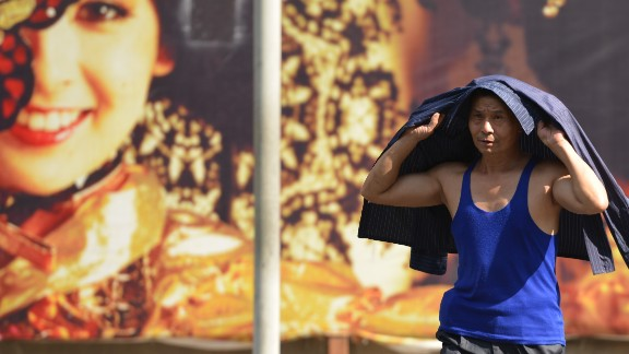 A pedestrian in Shanghai uses his jacket to shield himself from the sun on Wednesday, July 24.  Shanghai experienced its hottest July in at least 140 years, with temperatures reaching 35 degrees Celsius (95 degrees Fahrenheit) or higher on 25 days last month.  More than 10 people died of heatstroke in the city.