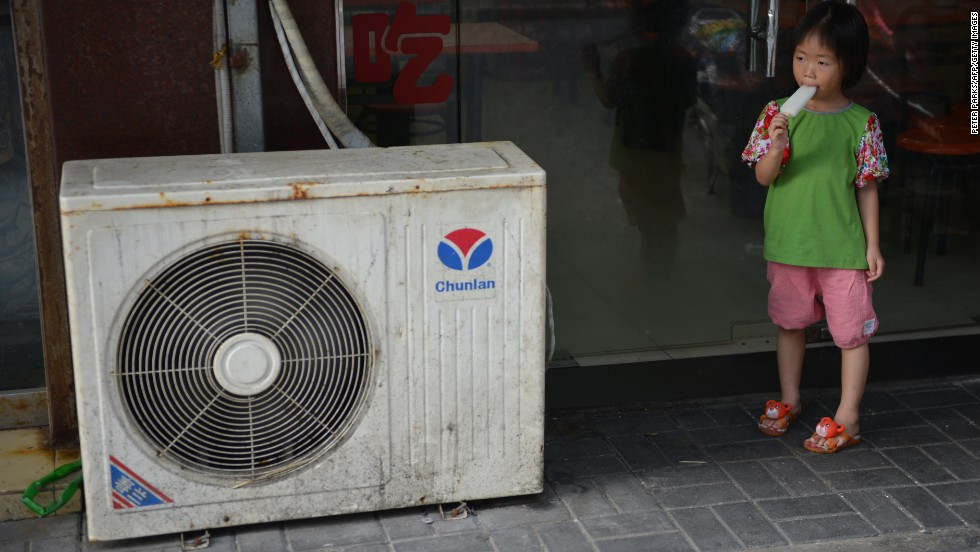 A young girl in Shanghai eats a popsicle next to an air conditioning unit to cool off on Tuesday, July 16.