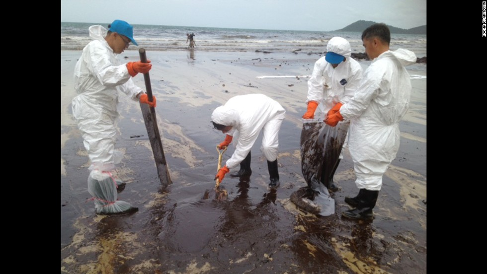 Workers continue to remove oil from Koh Samet on Thursday, August 1. PTT Global Chemicals says the Thai navy and approximately 300 PTT workers are continuing to clean up the area.