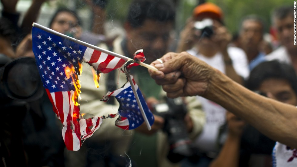 A woman burns American flags during a protest in support of Bolivian President Evo Morales in front of the U.S. embassy in Mexico City on July 4. Leftist Latin American leaders and activists were fuming after some European nations temporarily refused Morales' plane access to their airspace amid suspicions Snowden was aboard.