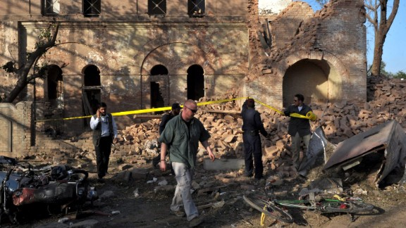 Officials examine the aftermath of a terrorist attack outside the U.S. Consulate in Peshawar, Pakistan, on April 5, 2010. The coordinated attack involved a vehicle suicide bomb and attackers who tried to enter the consulate by using grenades and weapons fire. Two consulate security guards and at least six others were killed.
