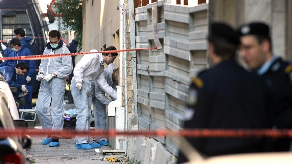 A bomb squad team collects evidence at a construction site where a rocket was launched near the U.S. Embassy in Athens, Greece, on January 12, 2007. The anti-tank missile tore through the embassy, but there were no injuries.