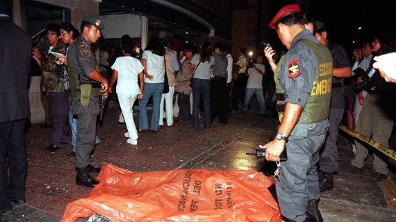 Police officers stand next to the body of a victim after a car bomb exploded on March 20, 2002, at a shopping center near the U.S. Embassy in Lima, Peru, killing nine people.