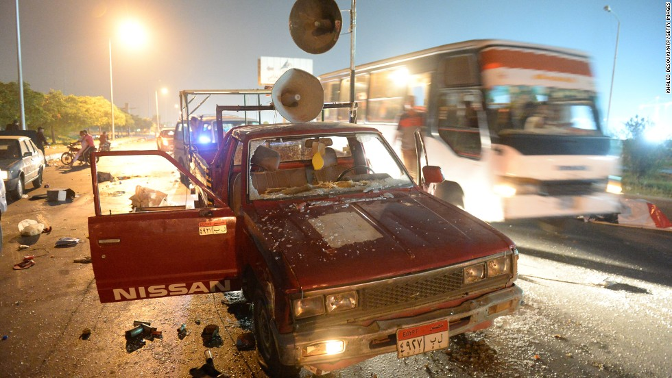 "A bus passes a destroyed pickup truck with loudspeakers that was used by supporters of ousted Egyptian President Mohamed Morsy on Friday, August 2. The supporters and security forces clashed in Sixth of October City in Giza, south of Cairo, after the government ordered their protest camps be broken up. <a href=""http://www.cnn.com/2013/08/15/middleeast/gallery/egypt-violence-august/index.html"" target=""_blank"">Look at the latest violence in Egypt.</a>"