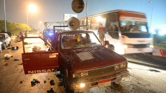 A bus passes a destroyed pickup truck with loudspeakers that was used by supporters of ousted Egyptian President Mohamed Morsy on Friday, August 2. The supporters and security forces clashed in Sixth of October City in Giza, south of Cairo, after the government ordered their protest camps be broken up. Look at the latest violence in Egypt.