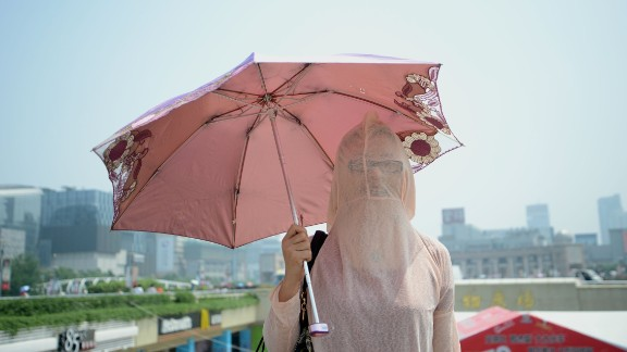 A woman wears her clothes backward against the scorching sun in Jinan, China, on August 4.