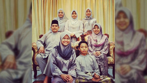 """Dina Syazwani Sipal Anuwar, a 24-year-old teacher from Selangor in Malaysia, took this photo of her family celebrating Eid last year. The photo means a lot to her as it was the last Eid she was able to spend with her father Sipal, a policeman, who unexpectedly passed away in January 2013. It was also the first time the family had ever managed to color coordinate their outfits. """"I think it was one of the signs that father would be leaving us, last Eid we could take a perfect photo as a whole family,"""" said  Dina, pictured top left. This year the family have decided to all wear pink."""