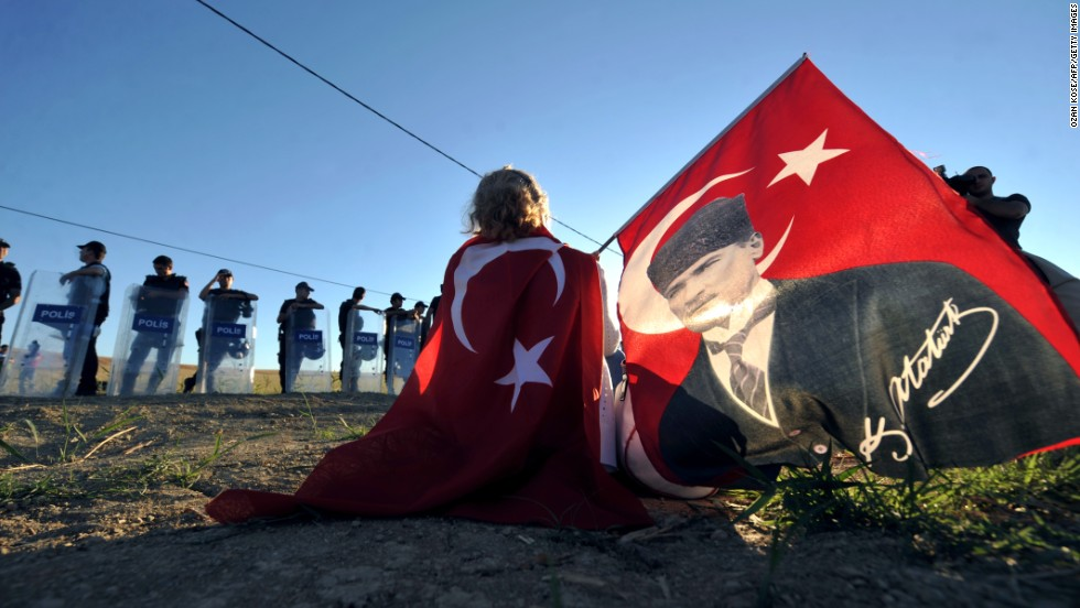 "AUGUST 6 - SILIVRI, TURKEY: Holding a portrait of Mustafa Kemal Ataturk, Turkey's first president, a protester sits in front of police forces blocking access to a courthouse in Silivri, near Istanbul, on August 5. <a href=""http://cnn.com/2013/08/05/world/europe/turkey-ergenekon-verdict/?hpt=wo_c2"">Ilker Basbug, the former head of Turkey's military, was sentenced to life in prison Monday.</a> He is the most prominent figure accused of trying to overthrow the government."