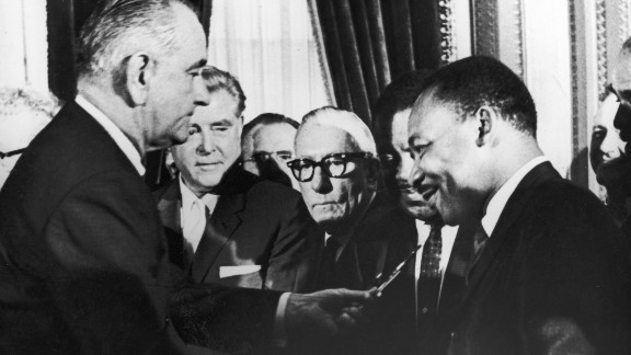 U.S. President Lyndon B. Johnson hands a pen to the Rev. Martin Luther King Jr. during the signing of the Voting Rights Act on August 6, 1965. The landmark legislation helped protect minorities who had previously encountered unfair barriers to voting.