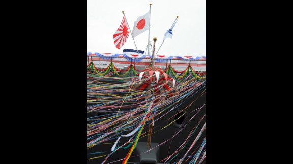 Japan's national flag, center, is displayed next to the flag for Japan's Maritime Self-Defense Force, left, above decorations streaming from the ship.