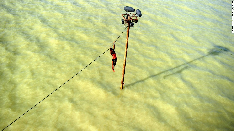 A person dangles from a power line before diving into the Ganges River in Allahabad, India, on Tuesday, August 6, after heavy monsoon rains.
