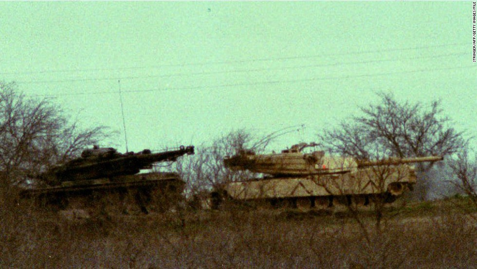 Two M1 Abrams tanks sit in the underbrush about 200 yards from the Branch Davidian compound on March 10, 1993.