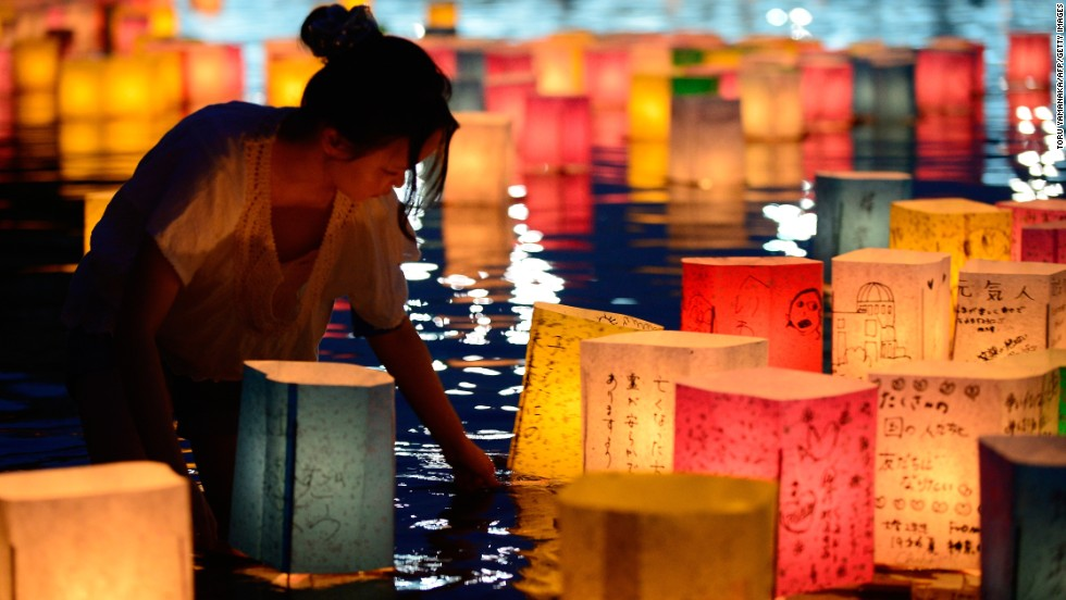 "AUGUST 7 - HIROSHIMA, JAPAN: A woman floats paper lanterns on the Motoyasu River in memory of the victims of the 1945 atomic bombing of Hiroshima, western Japan. Crowds gathered in front of the Atomic Bomb Dome at the Peace Memorial Park in Hiroshima on August 6 to mark the 68th anniversary. The bombing <a href=""http://cnn.com/2013/08/06/world/asia/btn-atomic-bombs/index.html?hpt=ias_mid"">claimed the lives of more than 270,000 people.</a>"