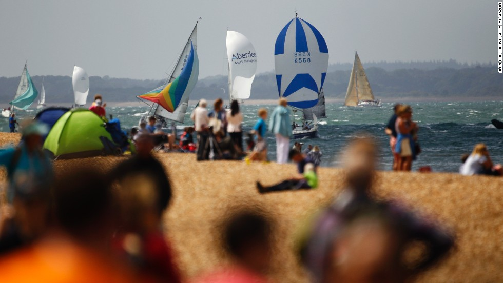 Spectators watch from the shore as yachts compete in Cowes Week,on the Isle of Wight in southern England. More than 8,000 sailors compete from around the world in the historic regatta.