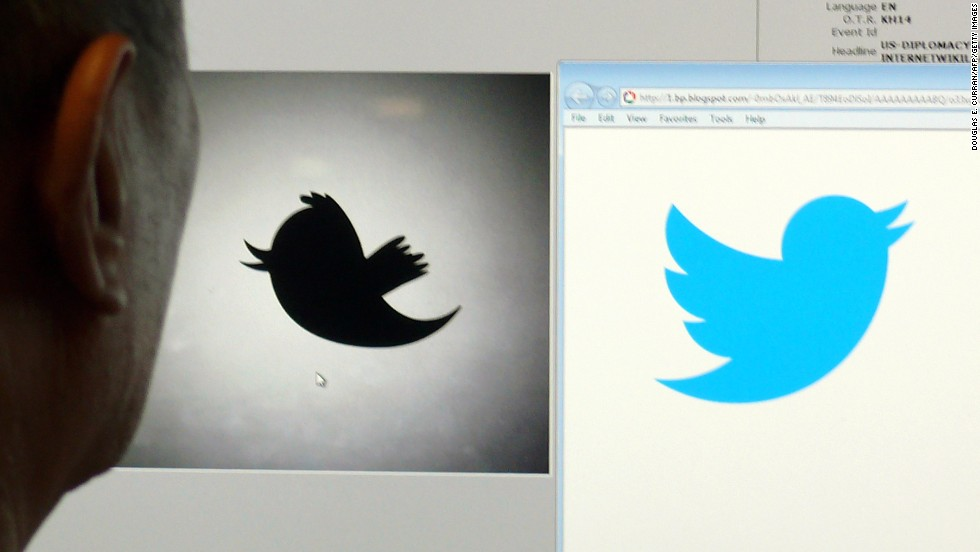 A man looks at a computer monitor showing the old and new Twitter logos. The social networking company dropped the name and now uses the bird image alone.
