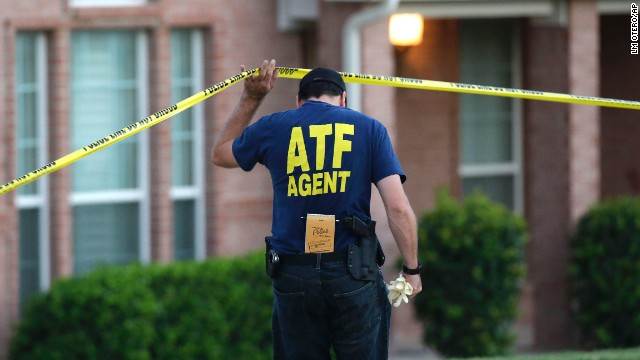 An ATF agent ducks under crime scene tape at a house in DeSoto, Texas.