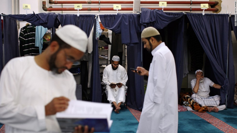 Men gather around private cubicles at the East London Mosque in London on Wednesday, August 7, the last night of Ramadan.