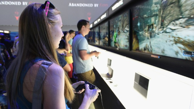"A visitor to this year's Electronic Entertainment Expo in Los Angeles plays a demo of ""Warframe"" at the Sony Playstation 4 booth."