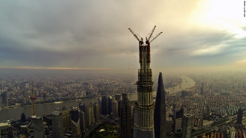 "AUGUST 5 - SHANGHAI, CHINA: Work on the main structure of the Shanghai Tower was completed on August 3, when a crane placed a steel beam 580 meters above the ground. China's construction boom gives rise to some of the world's tallest buildings. <a href=""http://cnn.com/2013/08/05/business/china-sky-city-skyscraper-index/index.html?hpt=ias_t5"">But some say it can also bring economic bust.</a>"
