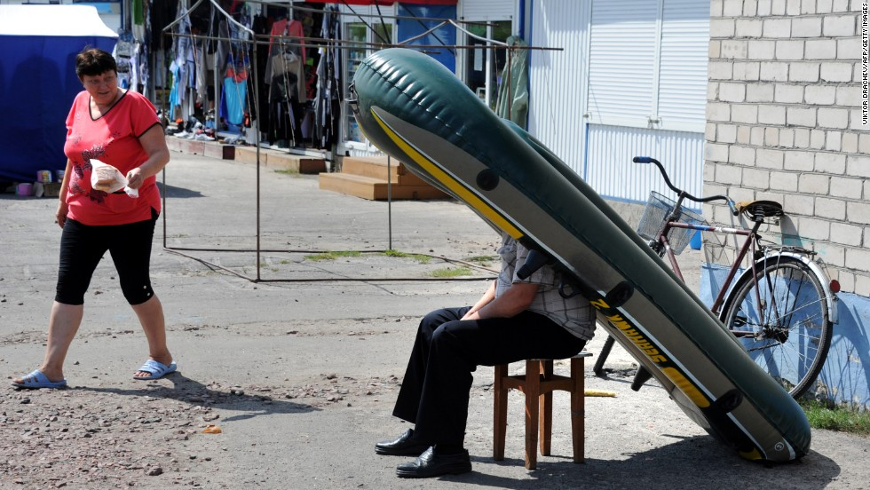 A street vendor steers clear of the hot sun under an inflatable boat in Zhitkovichi, Belarus, on August 7.
