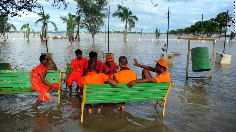 Hindu pilgrims sit on a partially submerged bench outside the Bade Hanuman Temple as water from the Ganges and Yamuna rivers recedes in Allahabad, India, on August 10.