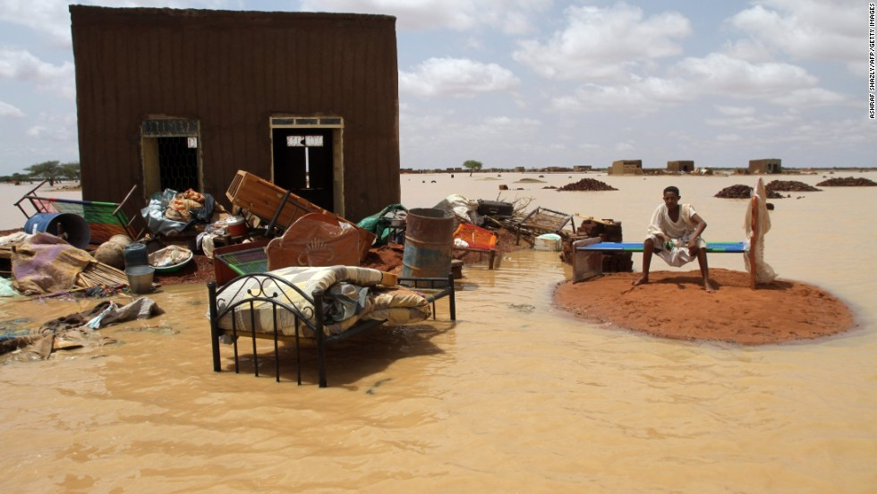 A man sits next to his house in a flooded street outside Khartoum, Sudan, on Saturday, August 10.