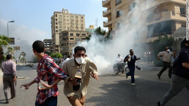 Egyptian Muslim Brotherhood supporters run from tear gas fired by Egyptian police as they try to disperse supporters of Egypt's ousted president Mohamed Morsi in a street leading to the Rabaa al-Adawiya protest camp in Cairo on August 14, 2013. Egypt's Muslim Brotherhood said at least 250 people were killed and over 5,000 injured in a police crackdown on two major protest camps held by supporters of ousted president Mohamed Morsi.