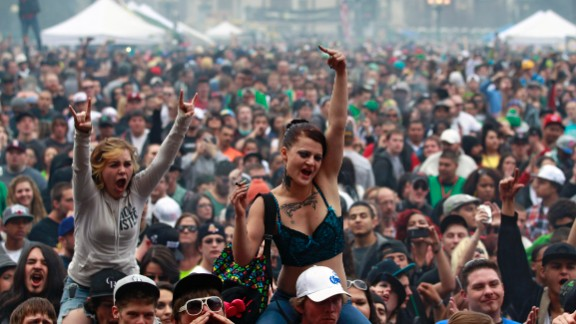 Members of a crowd numbering tens of thousands smoke and listen to live music at the Denver 420 Rally on April 20, 2013. Annual festivals celebrating marijuana are held around the world on April 20, a counterculture holiday.