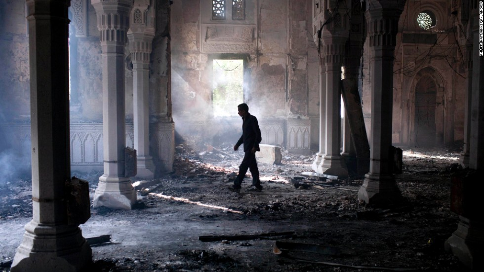 A man walks inside the burned-out Rabaa Al-Adawiya mosque in Cairo on August 15, 2013.