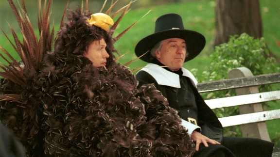 """Billy Crystal, left, dressed as a turkey, sits on a bench with De Niro, dressed as a pilgrim, during the filming of a Thanksgiving-themed """"I Love New York"""" commercial in 2001."""