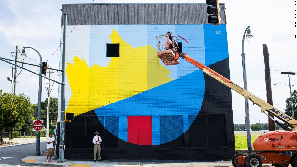 An artist hitches a ride to the top of a wall. Twenty artists converged on Atlanta this month as part of an annual street art conference called Living Walls.