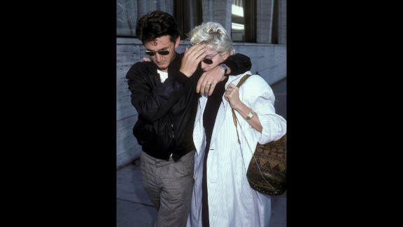 Then-husband Sean Penn shields Madonna from the paparazzi during a lunch break in New York on August 13, 1986.
