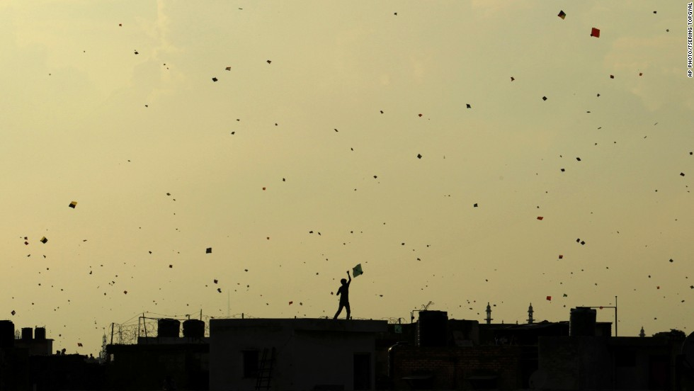 "AUGUST 16 - NEW DELHI, INDIA: Against a yellowing sky, a boy stands on a roof and flies a kite, which flocks with other kites in traditional celebration of India's<a href=""http://cnn.com/2013/08/15/world/asia/india-activists-independence-day-twitter/""> 66th Independence Day</a> on August 15. The day marks the end of the British rule on the country in 1947."