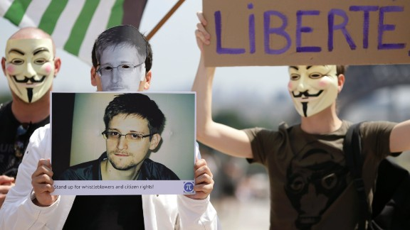 """Supporters of Snowden at a demonstration in Paris. """"We can't ignore the threat to our civil liberties by giving the government vast powers any more than we can ignore the fact that we live in a dangerous world,"""" says Neil Richards."""