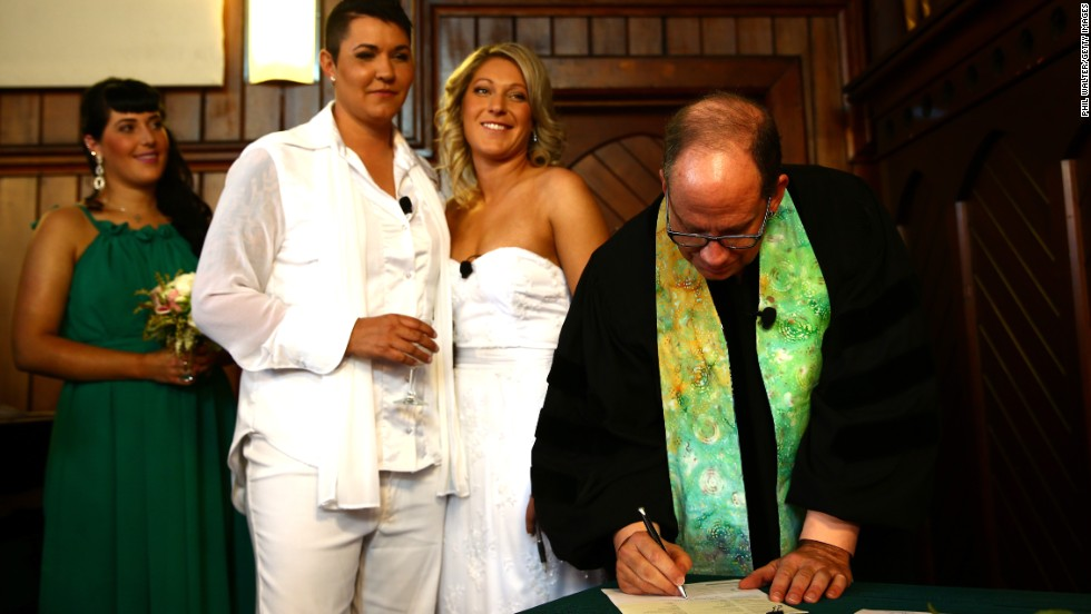 The Rev. Matt Tittle signs the marriage certificate for Natasha Vitali and Melissa Ray on August 19 in Auckland.