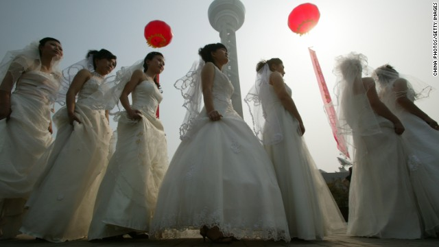 Brides line up during a collective wedding ceremony for 100 migrant worker couples  in Nanjing China.
