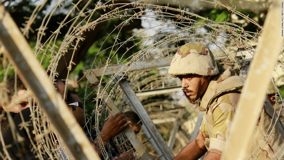 A soldier sets up barbed wire in anticipation of protesters outside the constitutional court in Cairo on Sunday, August 18, 2013. During the previous week about 900 people -- security forces as well as citizens -- had been killed. Deaths occurred when the military used force to clear supporters of ousted president Mohamed Morsy from two sit-in sites in Cairo, and violence raged after Morsy supporters staged demonstrations.