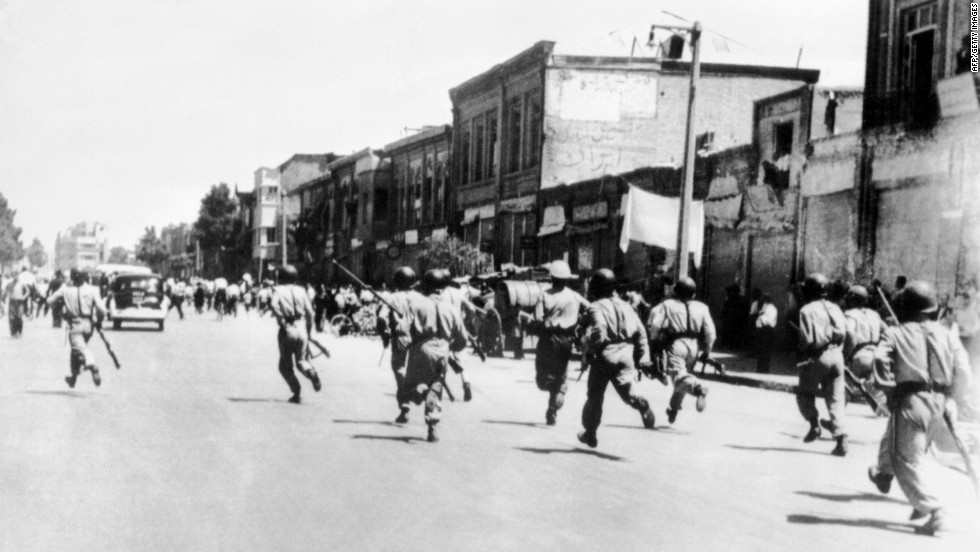Soldiers chase rioters during civil unrest in Tehran. Massive protests broke out across the nation in 1953.