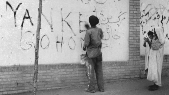 """A resident washes """"Yankee Go Home"""" graffiti off a wall in Tehran on August 21, 1953. Zahedi ordered a clean-up after the coup."""