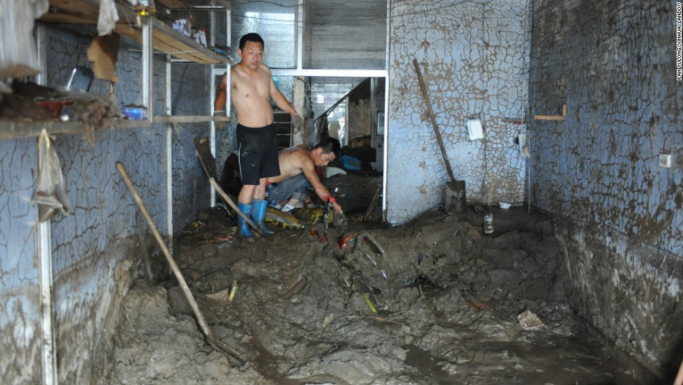 Men attempt to clean a building in Fushun City, China, on Tuesday, August 20. At least 107 people are dead in China after heavy rains inundated roads and farmland, the Chinese government says.