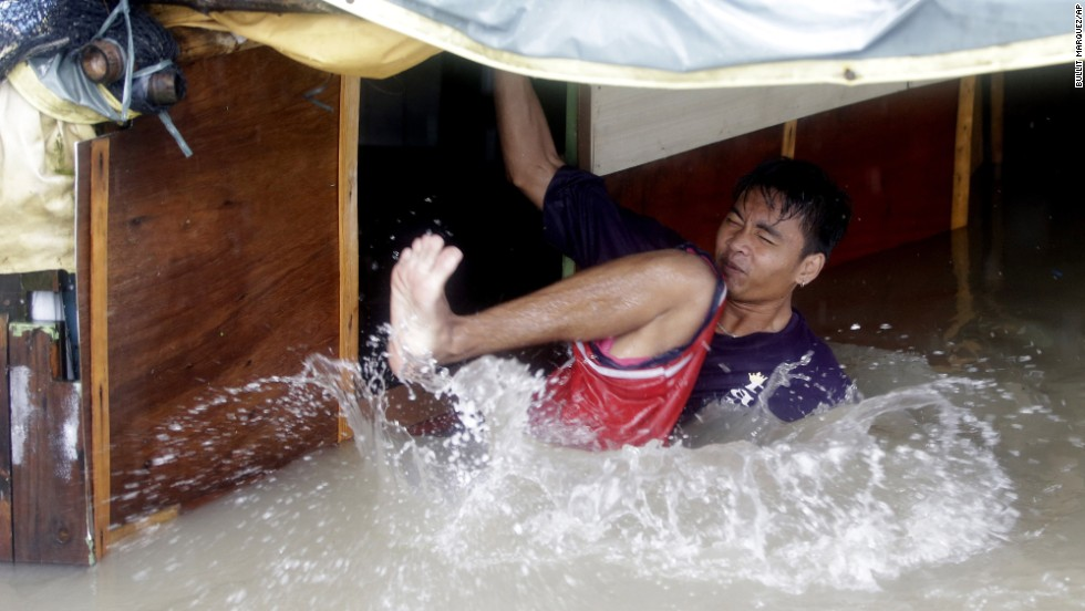A man falls as he tries to fix the roof of his flooded home in Binakayan on August 19.