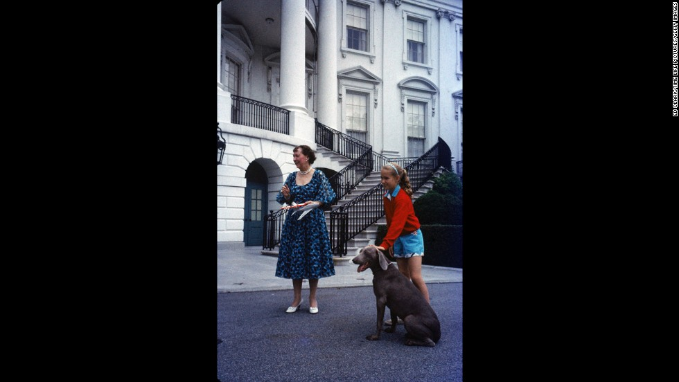 First lady Mamie Eisenhower and her granddaughter Barbara Anne Eisenhower stand with the family pet, Heidi, outside the White House.