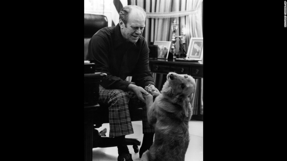 President Gerald Ford relaxes with his dog Liberty in the Oval Office in 1975.