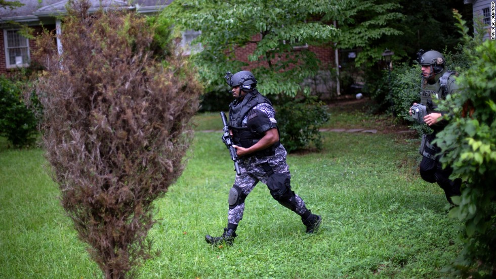 Dekalb County Police SWAT officers run though the front yard of a home toward the elementary school on Tuesday.