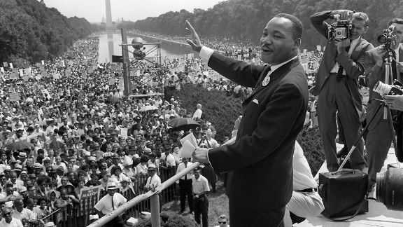 US civil rights leader Martin Luther King,Jr. (C) waves to supporters from the steps of the Lincoln Memorial 28 August 1963 on the Mall in Washington DC (Washington Monument in background) during the